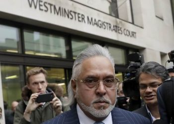 F1 Force India team boss Vijay Mallya has to leave the building after an alarm inside went off, before the start of his case on the the first day of his extradition case at Westminster Magistrates Court in London, Monday, Dec. 4, 2017. Mallya, the United Breweries Group chairman and co-owner of the Force India F1 team is wanted in India to face fraud allegations.  (AP Photo/Matt Dunham)